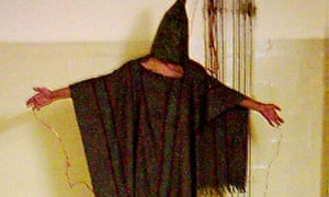 A detainee standing on a box with a bag on his head and wires attatched to him in late 2003 at the A