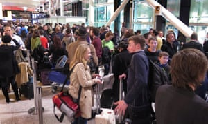 Passengers line up in Terminal Three as they wait for delayed flights at Heathrow Airport.