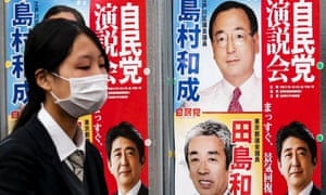 A woman walks past election posters for Japan's upcoming snap election in Tokyo, December 11, 2014.