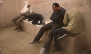 Migrants without papers sit in a holding cell at the US Border Patrol detainee processing center n McAllen.