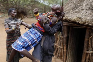 In a photograph by Siegfried Modola, a regular contributor to 20 photographs, a man holds a girl as she tries to escape an arranged marriage in Baringo County, Kenya. As Pokot tradition dictates, the future husband arrived at the girl's family home with the last settled dowry of livestock and a group of men to collect her. She was unaware of the marriage arrangements that her father had made as her family said she might have run away from home