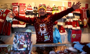 A souvenir seller shows off his Christmas jumper which looks remarkably similar to the Leicester City fan's jumper