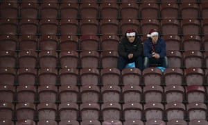 Burnley supporters wearing Christmas hats sit in the stands waiting for kick-off