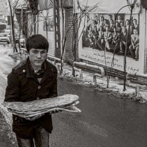A young man carries freshly baked barbari bread in Tehran, Iran.