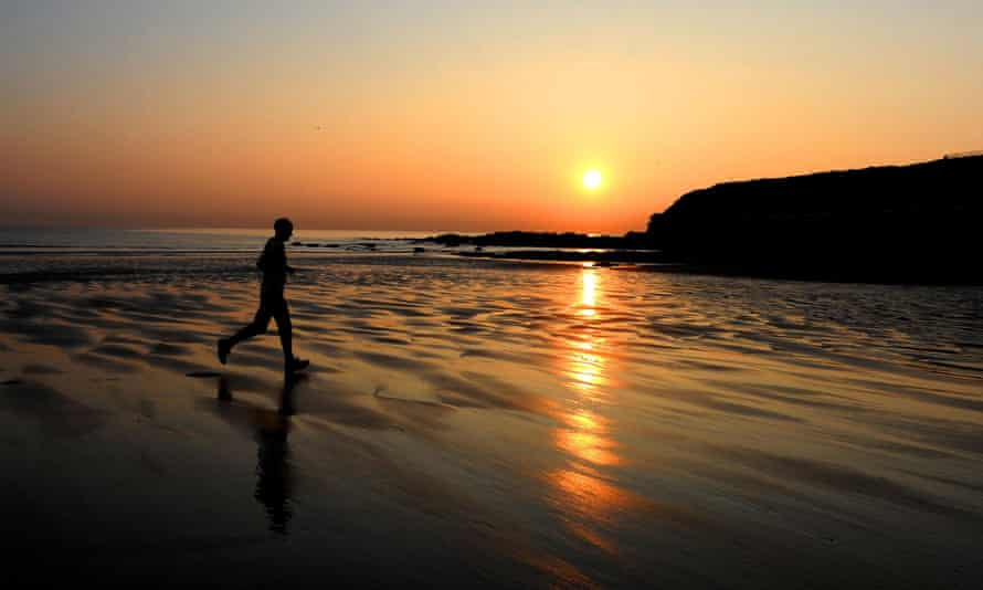A jogger runs as the sun rises on Tynemouth beach, Tyne and Wear. Physical exercise and better diet can help lower risks of dementia, says Age UK.