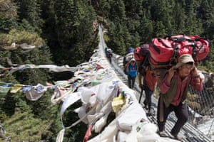 Sagarmatha National Park.Porters working for your agencies carrying clients bags across a bridge in Sagarmatha National Park, heading towards Namche Bazar. Regulations have been set in place, stating that porters should not carry loads over 30KG, but there is little enforcement of this rule. Porters earn approximately $10 per day on treks.