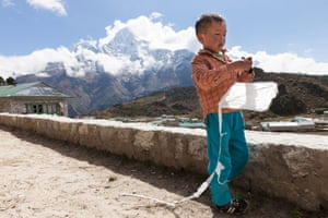 Khumjung.Tenba, 7, plays with his kite in his some town of Khumjung, where his aunt cares for him. After his father, Chhiring Ongchu Sherpa died in April, Tenbas mother went to work as a trekking guide to make money, leaving Tenba and his younger sister at home with their aunt. Traditionally only men work, supporting their whole family, whilst the women stay at home, often running teahouses.