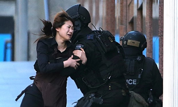 A hostage runs to armed tactical response police officers for safety after she fled a cafe under siege at Martin Place in Sydney