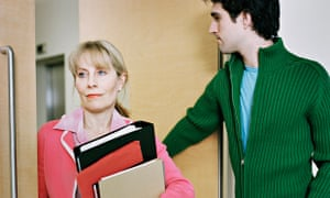Young man holds door open for older female colleague