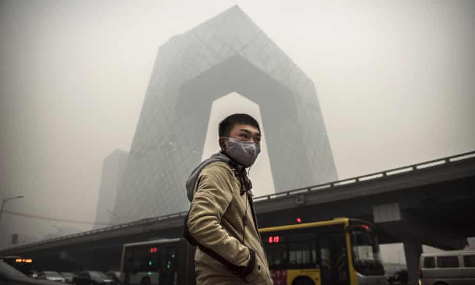 A Chinese man wears an anti-pollution mask near the China Central Television building in Beijing.