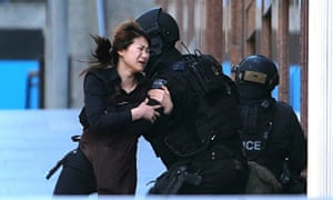Sydney, Australia A hostage runs to armed tactical response police officers for safety after she escaped from a cafe under siege at Martin Place in the central business district