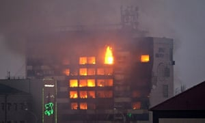 The media building burns as militants at