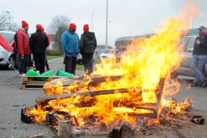 Workers and members of trade unions block a road leading to a Brussels airport catering company during a national strike in a protest over the government's planned pension reform and budget cuts at the Brussels Airport in Zaventem.