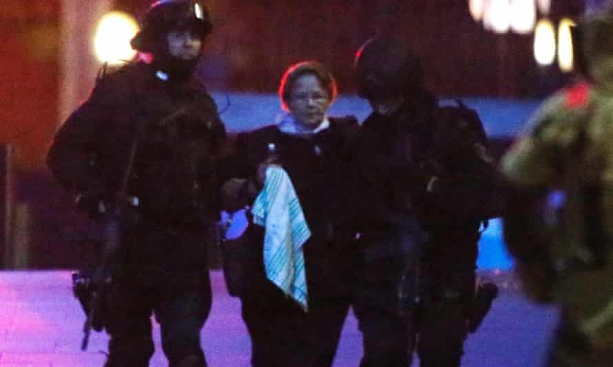Two heavily armed police officers assist a hostage away.
