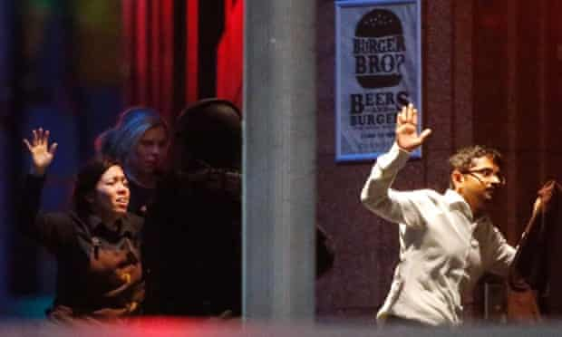 Hostages run past a police officer near Lindt Cafe in central Sydney.