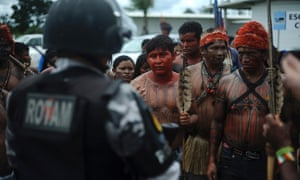 Indians from the Munduruku, Juruna, Kayapo, Xipaya, Kuruaya, Asurini, Parakana, and Arara tribes in Tapajos and Teles Pires river basins face a riot police officer as they invade the main construction site of the Belo Monte hydroelectric dam site in protest against the dam's construction, in Vitoria do Xingu, near Altamira in Para State, May 2, 2013.