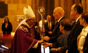 Archbishop of Sydney, Most Reverend Anthony Fisher shakes hands with Australian Governor General Peter Cosgrove during a mass to pay respect to the victims of the Martin Place siege.