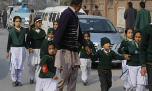 A plainclothes security officer escorts students rescued an army school during a Taliban attack in Peshawar, Pakistan