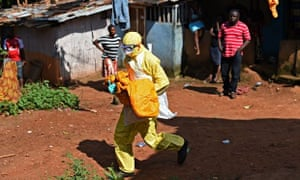 A Sierra Leonean health worker carries the body of a child for burial