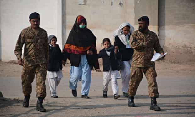 Schoolchildren rescued by the army leave following an attack at a school in Peshawar, Pakistan