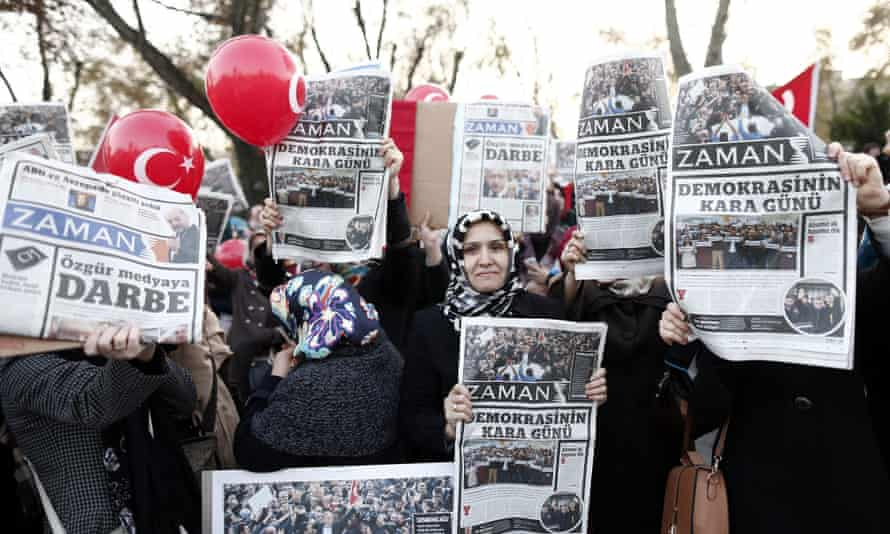 Supporters of the Hizmet movement of US-based Islamic cleric Fethullah Gulen hold copies of the Zaman newspaper as they take part in a demonstration a day after Turkish police began an operation targeting media supportive of the movement.