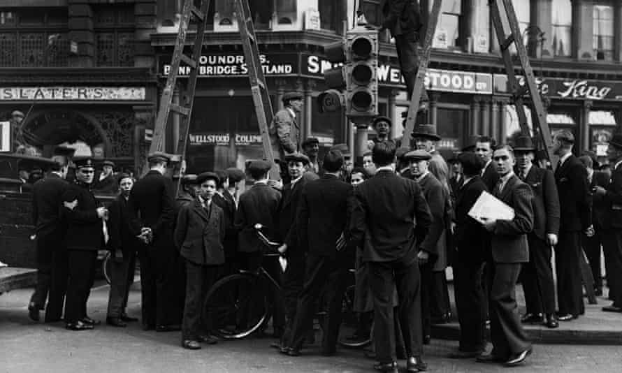 A crowd watches as new, automated traffic lights are erected at Ludgate Circus, London, in 1931.