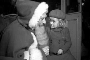 A little girl telling Santa Claus what she would like for Christmas at John Barkers store, London