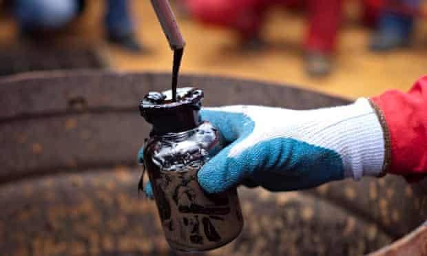 A worker collects crude oil sample at an oil well operated by Venezuela's state oil company PDVSA