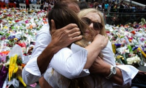 Tori Johnson's mother (right) is embraced as the siege victim's family visits the sea of flowers in Martin Place