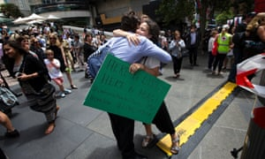 Sarah from Sydney administers free hugs to people after they visit the sea of flowers in Martin Place