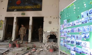 Pakistani soldiers walk amidst the debris in an army-run school a day after an attack by Taliban militants in Peshawar.