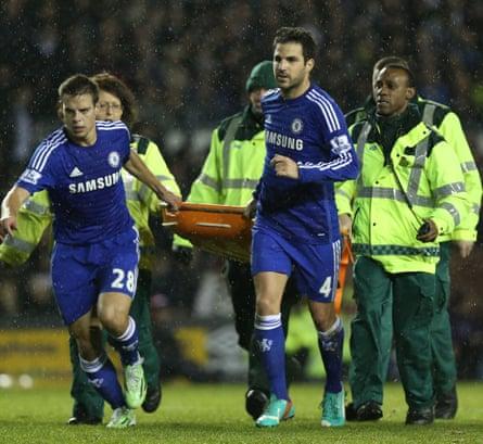 César Azpilicueta  and Cesc Fàbregas help carry Kurt Zouma off the field on a stretcher.
