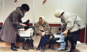 Trio of women trying on boots, shopping for imported shoes, at Luxe (Lyuks) department store in suburban Moscow, in 1989.