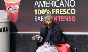A woman begs on the sidewalk outside a coffee shop in Mexico City.