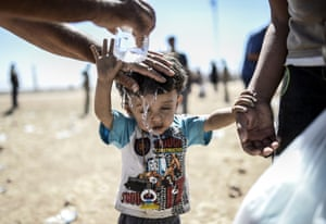 A Syrian Kurd pours water on a child after they crossed the border between Syria and Turkey near the southeastern town of Suruc in Sanliurfa province, 20 September 2014. Several thousand Syrian Kurds began crossing into Turkey a day earlier fleeing Islamic State fighters who advanced into their villages, prompting warnings of massacres from Kurdish leaders