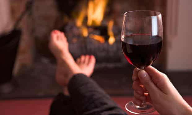 A pair of feet warming at a fireplace while holding a glass of wine