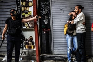 Istanbul, Turkey - 31 May A man protects a woman as they face a police officer dispersing protesters who gathered on the central Istoklal avenue near Taksim square, as the police blocked access to the square during the one year anniversary of the Gezi park and Taksim square demonstrations