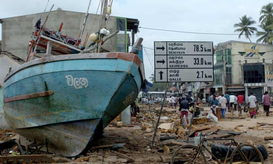 Sri Lankan residents walk past a fishing boat marooned on a road after a massive tidal wave struck the southern district of Galle, taken on 27 December 2004