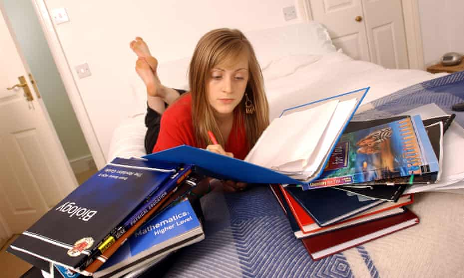 Student with a pile of biology books.