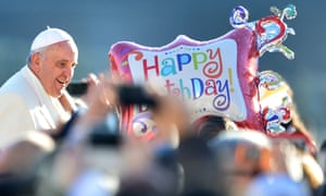 Pope Francis passes by a balloon reading Happy Birthday as he greets the crowd