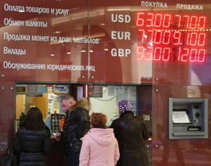 People queue at an exchange office in front of electronic information board displaying currency exchange rates, in Moscow, 17 December 2014.