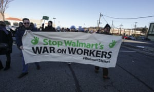 Marchers hold Walmart Strikers banner in Walmart parking lot in New Jersey in November 2014. They were protesting against employee mistreatment.