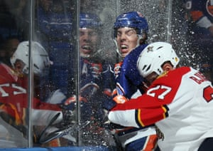 1 April: Travis Hamonic of the New York Islanders is hit into the glass by Nick Bjugstad of the Florida Panthers during the first period of their ice hockey match at the Nassau Veterans Memorial Coliseum in Uniondale, New York