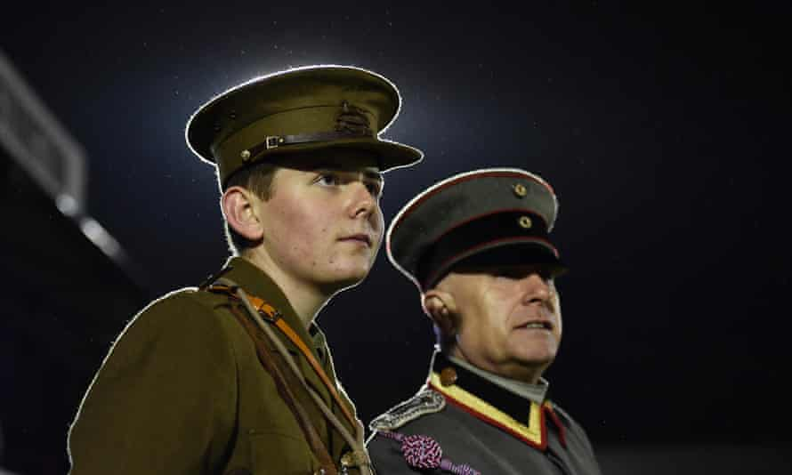 Two men wearing replica uniforms watch the football match between the British army and German forces at Aldershot Town FC.