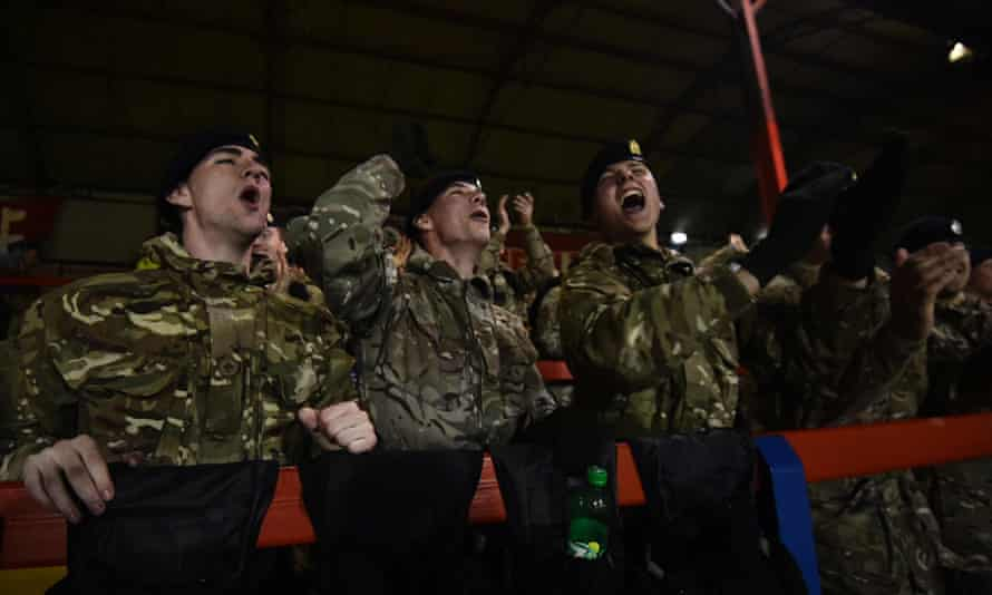 British army personnel celebrate the winning goal as they watch the commemorative football match.