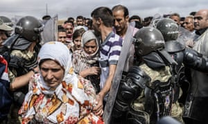 <strong>Mursitpinar, Turkey</strong><br>28 September: Turkish soldiers control the crossing gate as Syrian Kurdish people try to pass. Tens of thousands of Syrian Kurds flooded into Turkey fleeing an onslaught by the jihadist Islamic State (IS) group