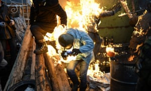 Protesters catch fire as they stand behind burning barricades during clashes with police February 20, 2014 in Kiev