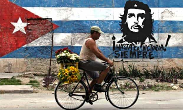A man rides his bicycle past a mural of rebel hero Ernesto 'Che' Guevara and a Cuban flag in Havana