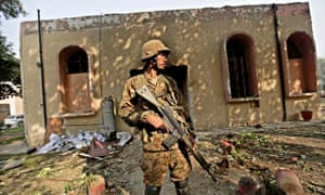 A Pakistani army soldier stands guard outside the Army Public School attacked by the Taliban.