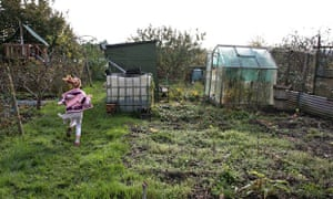 Girl running away from us on an allotment